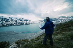 One person looking at trekking map, dramatic sky at dusk, lake and snowy mountains, nordic cold feeling Royalty Free Stock Photo