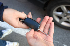 One person sells car and gives the key to the new owner Stock Photo