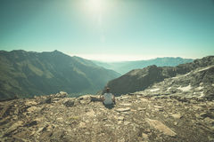 One person sitting on rocky terrain and watching a colorful sunrise high up in the Alps. Wide angle view from above with glowing m. Ountain peaks in the Royalty Free Stock Image
