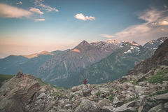One person sitting on rocky terrain and watching a colorful sunrise high up in the Alps. Wide angle view from above with glowing m. Ountain peaks in the Royalty Free Stock Photos