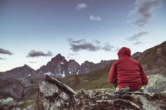 One person sitting on rocky terrain and watching a colorful sunrise high up in the Alps. Wide angle view from above with glowing m. Ountain peaks in the Stock Image