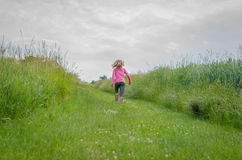 One person in the sprinting in the green meadow. Girl with long blond hair back view walking in rural path stock photos