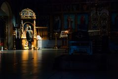 Lonely prayer in the temple. One person stands in the darkened room of the Orthodox church in prayer before the icon Royalty Free Stock Image