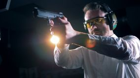 Man standing with a pistol in hands in a shooting room, shooting range. One person trains in a room, aiming with a gun stock video footage