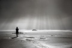 Person walking toward sunbeams Royalty Free Stock Photo
