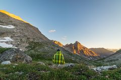 One person watching sunset in the Alps. One unrecognizable person covered by blanket  sitting and watching sunset high up in the Alps. Wide angle view from above Royalty Free Stock Photography