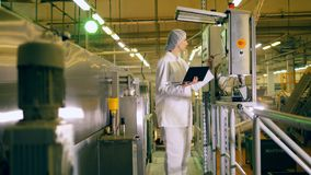 One person works with factory equipment in a food production facility.