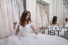 One person, young bride, looking at herself in mirror,. Bridal salon, wearing gown Royalty Free Stock Photography