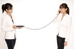 One The Phone 2. As asian businesswoman talks on the phone as the other holds the base Royalty Free Stock Images