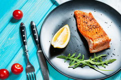 One piece of baked salmon with lemon on a black plate. Blue wood background.  Royalty Free Stock Photography