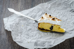 One piece of breton cake with plums and meringue on a wooden table Stock Photo