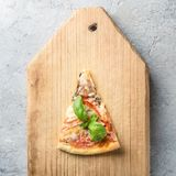 One piece of Italian pizza with tomatoes mushrooms bacon and che. Ese and basil leaves on wooden background cutting board kitchen board Food macro close-up and Royalty Free Stock Photography