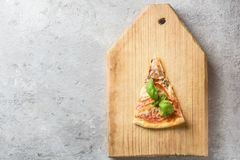 One piece of Italian pizza with tomatoes mushrooms bacon and cheese and basil leaves on wooden background cutting board. Kitchen board Food macro close-up and Royalty Free Stock Image