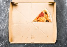 One piece of pizza in cardboard pizza box Top view of empty box with copy space on dark concrete stock image