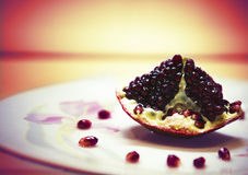 One piece of red pomegranate on white plate Royalty Free Stock Image