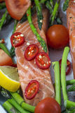 One piece of salmon with green asparagus, tomato Stock Images