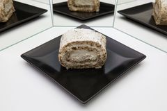 One piece of walnut roll with whipped cream on a black plate. Reflection in the mirror Royalty Free Stock Images