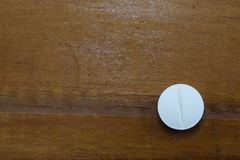 One pill that the doctor wrote from the illness lie on the table. Background Royalty Free Stock Photo