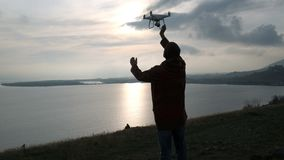 One pilot controlling the flying copter at sunset. Back view of one hiker with radio controlled multirotor helicopter and keeping aircraft. Guy standing near stock footage