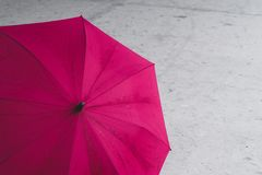 Pink colored, open umbrella lying open on ground royalty free stock images