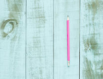 One pink pencil on blue wooden background Royalty Free Stock Image