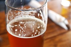 One Pint of Beer Marked Glass. Closeup of beer in a pint glass on a table. The glass is marked with the measurement for `one pint of beer royalty free stock photo