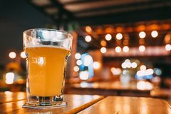 One pint of beer on restaurant table with copy space on blur bokeh background. Happy event celebrations, nightlife at pub concept Stock Image