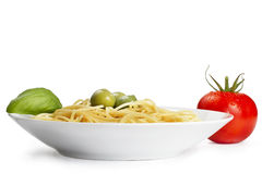 One plate with pasta some olives one tomato and ba. Silikum on white background royalty free stock images