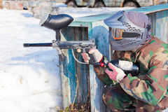 Player in a paintball aims for shelter in the game Royalty Free Stock Photo