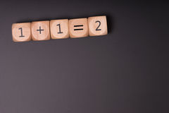 One plus one. Wooden cube with one plus one equals two Stock Photos