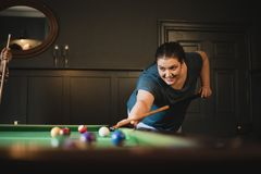 One in the Pocket. Small group of female friends playing a game of pool in a games room in a house royalty free stock photo