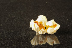 One popcorn kernel on a black background Royalty Free Stock Images