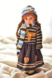 One porcelain doll standing on a brown deck. One porcelain doll with white background and a lot of copy space. Not so new. Old-looking doll Royalty Free Stock Images