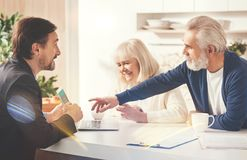 Positive old couple meeting with their insurance agent. This one. Positive elderly couple sitting in the kitchen while meeting with their insurance agent Royalty Free Stock Images