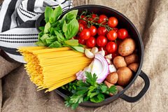 One pot pasta with basil, cherry tomatoes, red onion, garlic, parsley, mushrooms. Stock Image