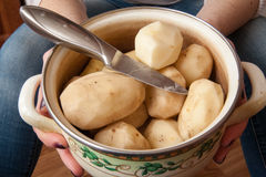 One potato is peeled with a kitchen knife Stock Photos