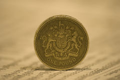 One pound coin on newspaper. Pound coin on a newspaper showing stock market tables Stock Photography