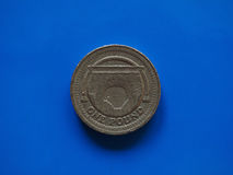 One Pound GBP coin, United Kingdom UK over blue. One Pound GBP coin, currency of United Kingdom UK over blue background Stock Photos