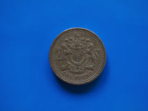 One Pound GBP coin, United Kingdom UK over blue. One Pound GBP coin, currency of United Kingdom UK over blue background Royalty Free Stock Images