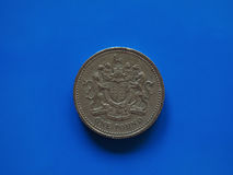 One Pound GBP coin, United Kingdom UK over blue. One Pound GBP coin, currency of United Kingdom UK over blue background Royalty Free Stock Photo