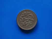 One Pound GBP coin, United Kingdom UK over blue. One Pound GBP coin, currency of United Kingdom UK over blue background Royalty Free Stock Photography
