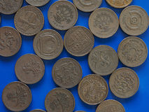 One Pound GBP coin, United Kingdom UK over blue. Many One Pound GBP coins, currency of United Kingdom UK over blue background Royalty Free Stock Image