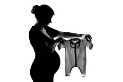 One pregnant woman holding baby clothes. One beautiful caucasian pregnant woman holding baby clothes in silhouette on studio isolated white background Royalty Free Stock Photo