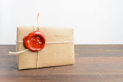 One present in craft paper with red sealing wax over wooden tabl Royalty Free Stock Image