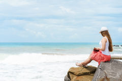 One pretty european woman is sittin on a stone close to shore of tropical sea and writing some idea, letter or job by Stock Images