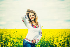 One pretty girl walkin in the yellow field with blue sky Stock Images