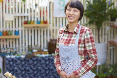 One Pretty Young Asian Florist Working in the Garden. One Beautiful Chinese Woman Working in the Florist`s Smile at Camera Royalty Free Stock Photo