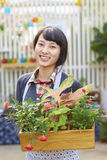 One Pretty Young Asian Florist Working in the Garden. One Beautiful Chinese Woman Working in the Florist`s Smile at Camera Royalty Free Stock Photography