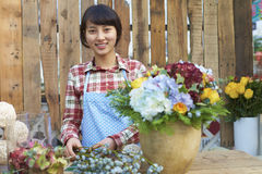 One Pretty Young Asian Florist Working in the Garden. One Beautiful Chinese Woman Working in the Florist`s Smile at Camera Royalty Free Stock Images