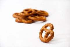 One pretzel and few pretzels on a white background Royalty Free Stock Photo